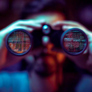 Hacker spying with binoculars